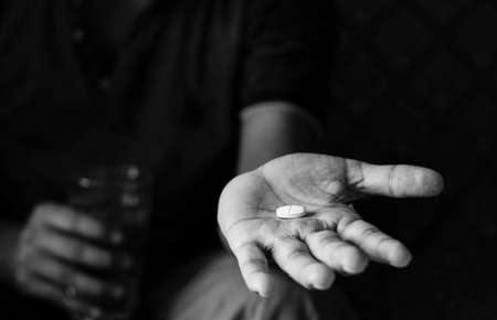 Black and white image of a tablet or pill on palm of an indian person with selective focus and glass of water on other hand at home