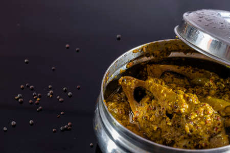 steamed ilish or hilsa fish with mustard paste in a steel tiffin box and mustard seeds on black background