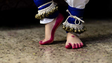 Close up of feet an Indian classical dancer wearing ghungroo or a musical anklet - group of small metallic bells strung together