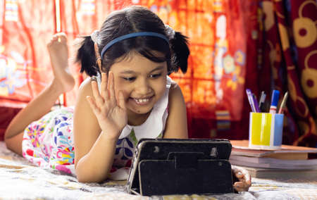 an Indian girl child with smiling face attending online class on tablet during COVID-19 pandemic outbreak Stock Photo