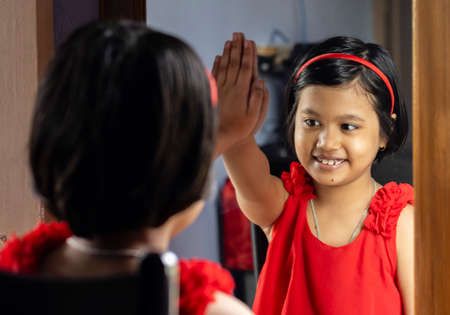 a cute Indian girl child in red dress making high five in front of mirror
