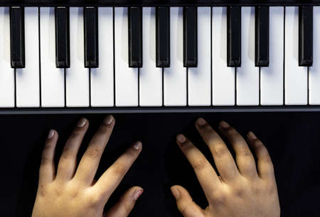 Top view of piano or keyboard with human hand in black background 版權商用圖片