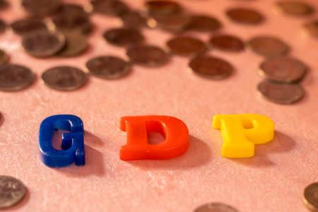 G D P colorful alphabets on pink surface around metal coins with shallow depth of field