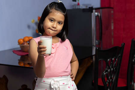 A cute little Indian / asian girl holding a glass full of milk with smiling face - healthy eating concept