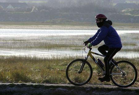 riverside: Back lit cyclist on riverside path