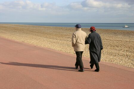 striding: Pensioner couple walking arm in arm along english coast seafront