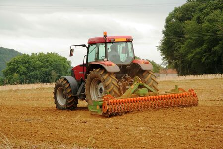 furrow: Red Tractor in Wheat field Stock Photo