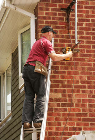 a frill: Workman with frill up ladder Stock Photo