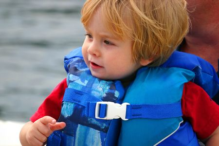 toddler boy wearing lifejacket by the water photo