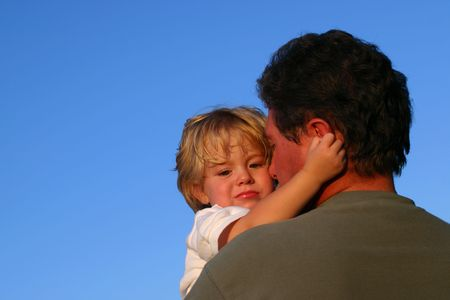 young boy being comforted by father Stock Photo