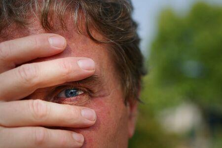 Mann mittleren Alters peeking vorläufig durch seine Hand  Standard-Bild