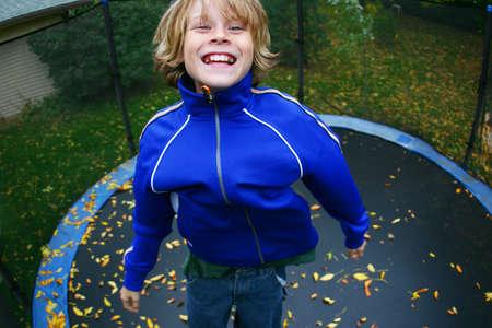 Boy springen hoch auf einem Trampolin  Lizenzfreie Bilder