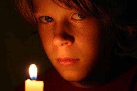 촛불로 불을 붙인 진지한 소년