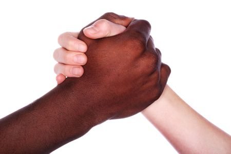 brotherhood: Hands of different races clasped in a handshake Stock Photo