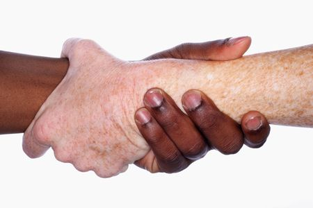 grabbing hand: two hands of different races clasped together Stock Photo