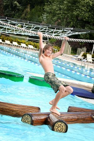 obstacle course: Teenager hanging from a rope while walking across floating logs  in a pool at a water park.