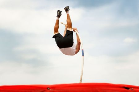 A pole vaulter jumps over bar with a cloudy sky in the background Stock Photo