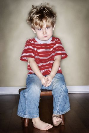 A young boy sits on his time out chair photo