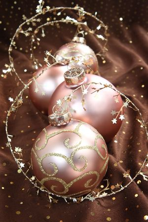 surrounds: Four glass Christmas ornaments in a arrangment on brown cloth with sparkles and a snowflake rope surrounds the group