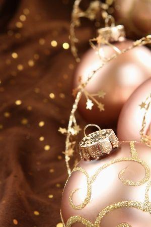 Cuatro adornos navide�os de vidrio en un acuerdo sobre tela marr�n con chispas y un copo de nieve cuerda rodea el grupo