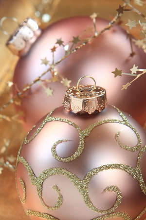 arrangment: Two glass Christmas ornaments in a arrangment on golden cloth with sparkles and a snowflake rope surrounds the group Stock Photo