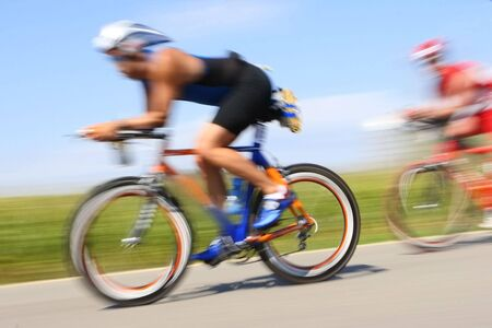 Two bicyclist race through the countryside. Their speed is excentuated by the motion blur
