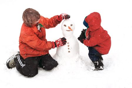 children at play: A teenager teaches his younger brother to build a snowman