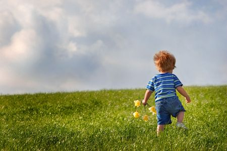 toddler walking: Young boy walks up a hill while holding a handfull of flowers. There are  storm clouds in the sky.