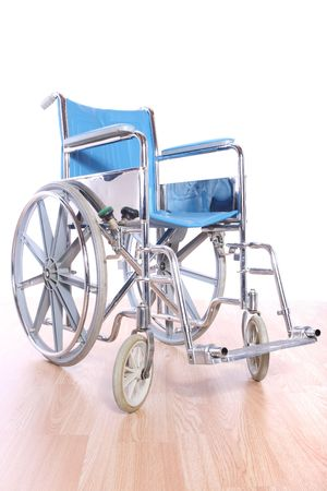 Wheel chair: an empty wheelchair sits on a wooden floor with a white background Stock Photo