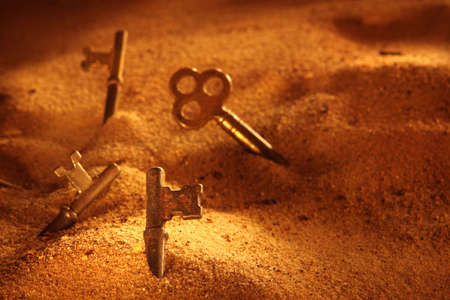 dramatically: a dramatically lit scene of skeleton keys in piles of sand Stock Photo