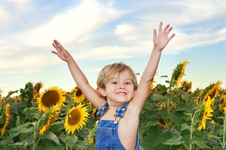 a young boy standing in front of a field of sunflowers