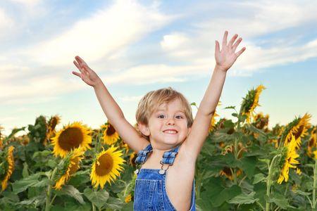 overol: un muchacho de pie delante de un campo de girasoles