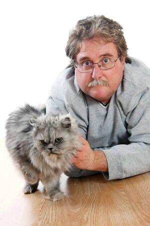 El hombre est� sentando en el piso con su gato