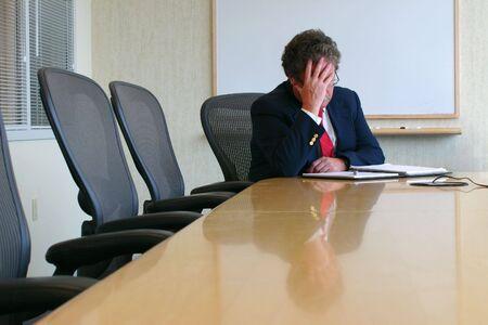 Hombre de negocios sentado en una sala de conferencias con la cabeza en su mano