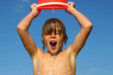 bucket water: Muchacho que descarga un cubo de agua en su cabeza contra un cielo azul Foto de archivo