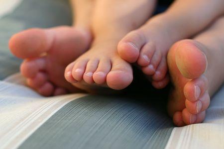 Primo piano di due piedi, mentre i ragazzi si siedono su una sedia Archivio Fotografico - 2754417