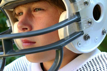 teenager thinking: Primer plano de un adolescente en un casco de f�tbol