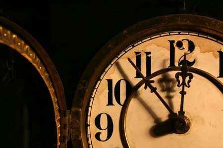 12 o'clock: Closeup of an antique clock face, the glass door is open. It is almost 12 o clock