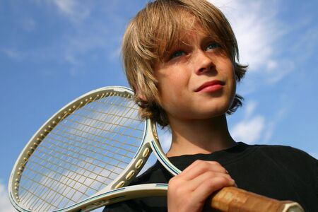 raquet: Closeup of boy playing tennis against a blue sky Stock Photo