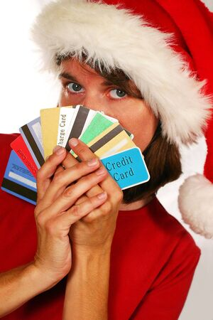 holiday spending: Adult woman in santa hat hiding behind credit cards (holiday spending and debt)