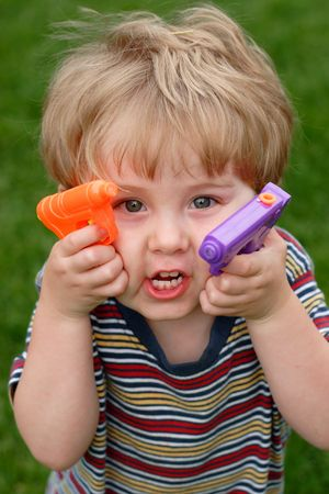 A young boy holds up two water guns Zdjęcie Seryjne
