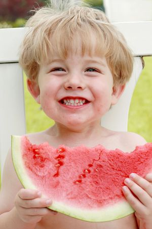 A boy smiles as he eats a piece of watermelon photo