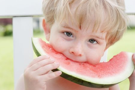 A young boy eats a piece of watermelon Stock Photo - 2758206