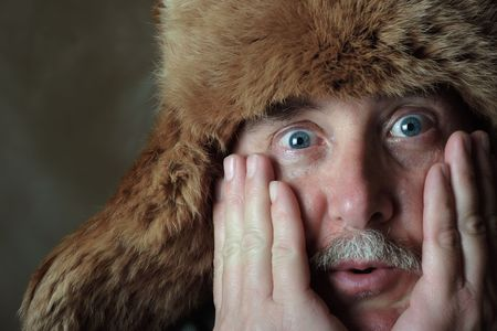 blustery: A middle aged man has an astonished look on his face while wearing  a fur hat