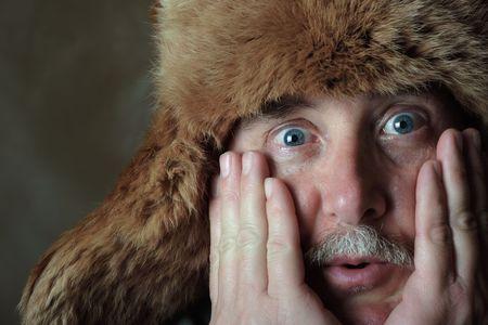 Un hombre de mediana edad tiene una mirada at�nita en su rostro al tiempo que lleva un sombrero de pieles  Foto de archivo