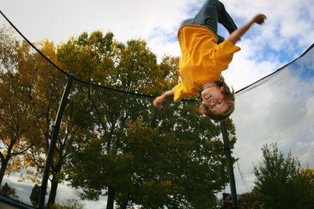BACKFLIP: a teenager does a backflip on a trampoline