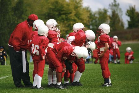 sideline: A young quarterback gives his team the gameplan before they line up Stock Photo