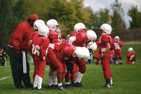 Un joven quarterback da a su equipo la gameplan antes de que se alinean  Foto de archivo