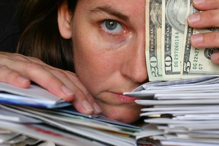 Closeup of a woman holding american bills resting her head on a pile of letters and bills
