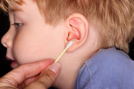 cotton swab: a young boy gets his ears cleaned out with a cotton swab Stock Photo